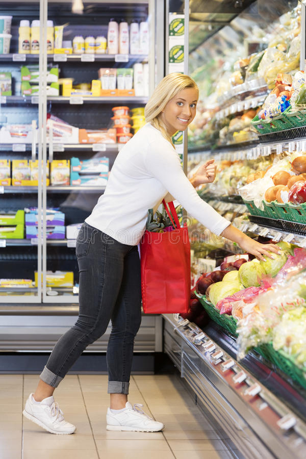Young Woman Buying Cabbage In Supermarket stock photography