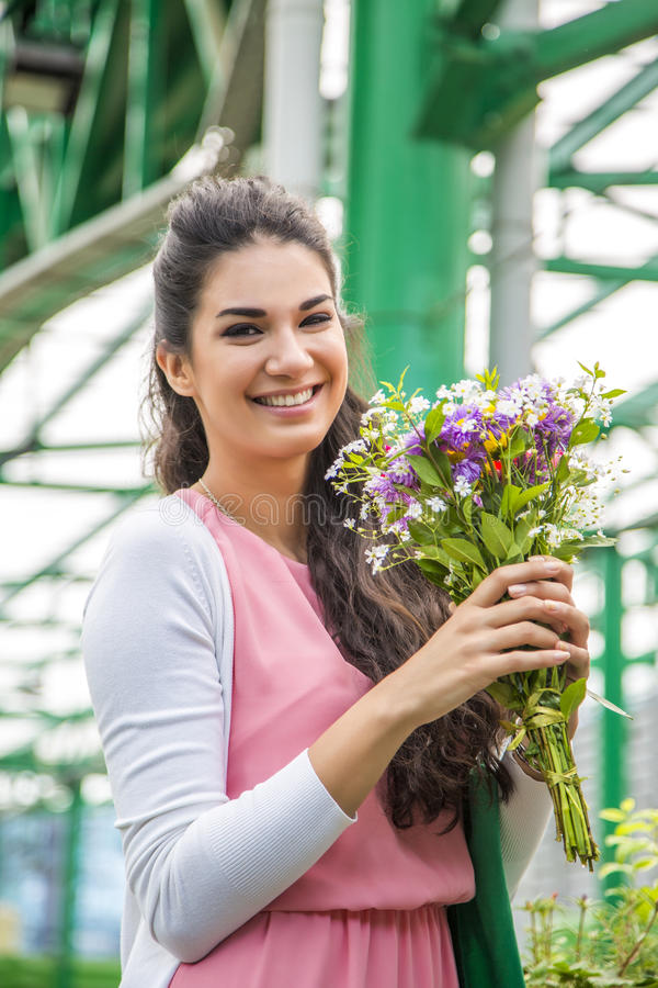 Young woman buying flowers. At market royalty free stock photography