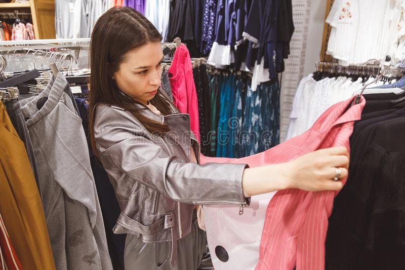 Young woman is buying a pink stripe suit.  stock photos