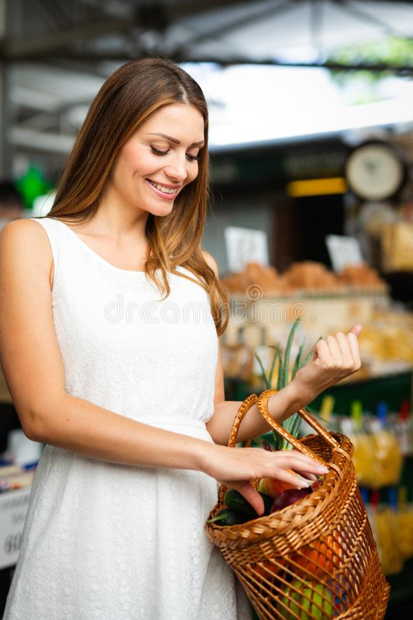 Young woman buying vegetable on stall at the market royalty free stock photos