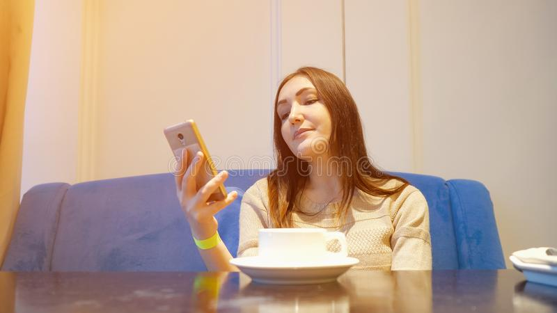 Young woman at cafe drinking coffee and using mobile phone stock image
