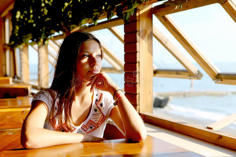 Young woman in cafe near sea royalty free stock photo
