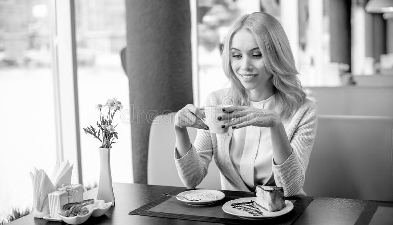 Young woman in Cafe. Portrait beautiful, happy,  young woman, sit in  Cafe and drink coffee or tea, black-and-white horizontal photo stock images
