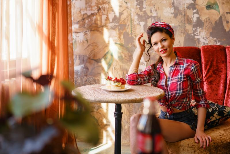 A young woman in a cafe sitting at a table with cakes, pin up royalty free stock photos