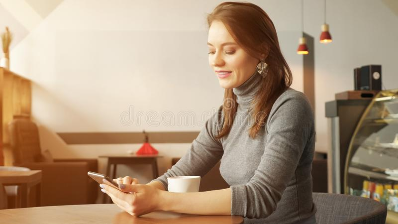 Young woman in cafe is typing a message on phone and drinking a cup of coffee waiting somebody. stock photos