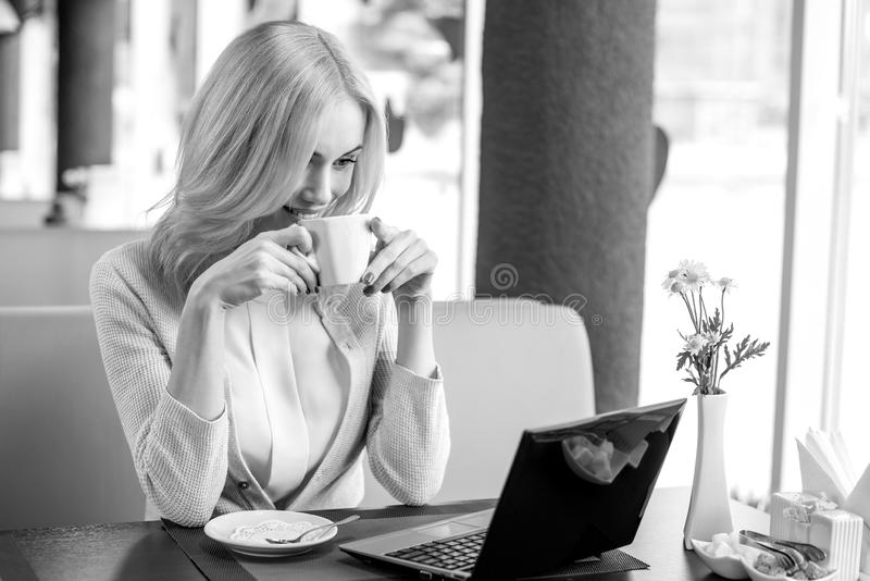 Young woman in Cafe. Very beautiful, happy, young woman, sit in Cafe with computer, horizontal portrait, black-and-white photo stock photos