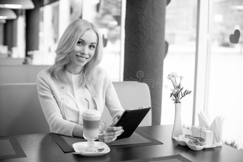 Young woman in Cafe. Very beautiful, happy, young woman, sit in Cafe with flatbed computer, horizontal portrait, black-and-white photo royalty free stock images