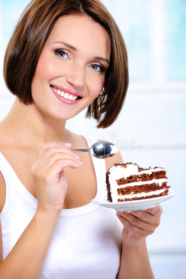 Young woman with a cake slice on a plate stock photos