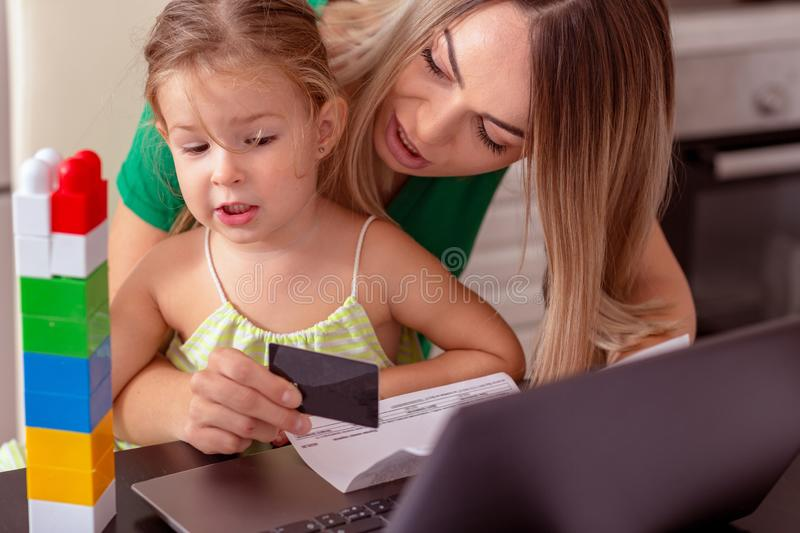 Young woman calculating finances at home with girl royalty free stock image