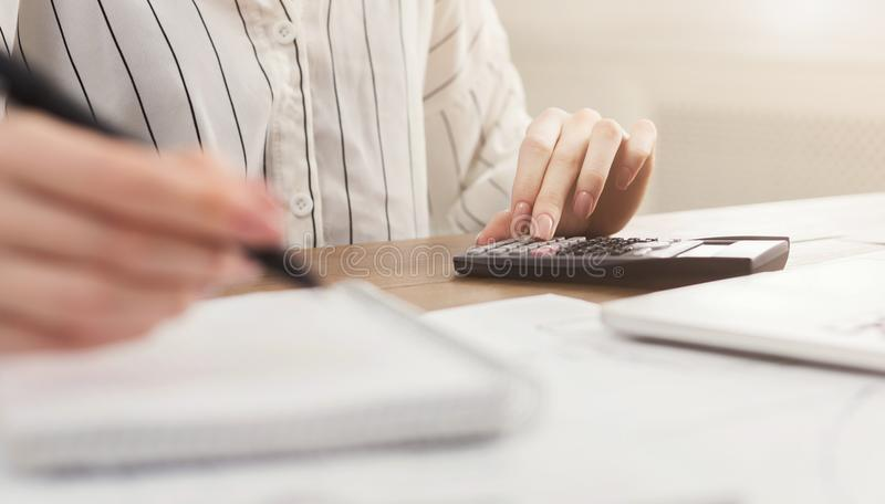 Woman with calculator counting and making notes stock photo
