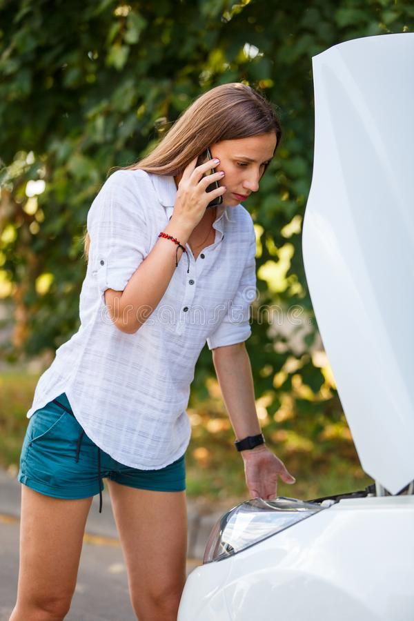 Young woman calling assistance about troubles with her car. Travel accident background royalty free stock photos