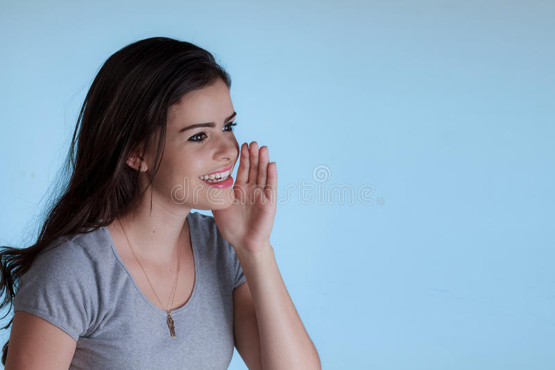 Young woman calling someone with a hand next to the mouth stock images