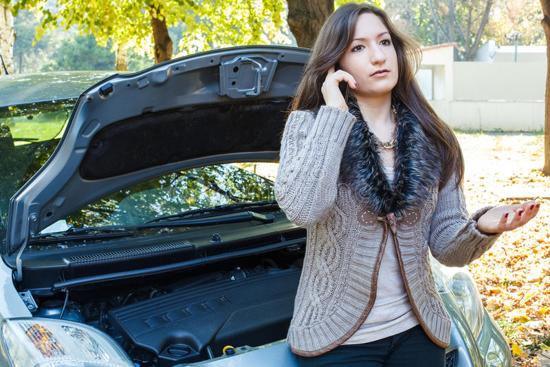 Young woman calls for assistance. Using her cell phone, after her car broke down . A young girl explains on the phone about car breakdown royalty free stock photo