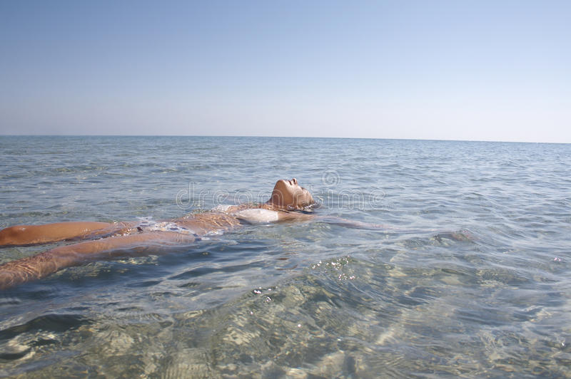 Young woman in the calm sea. Young woman resting in the calm sea royalty free stock photography