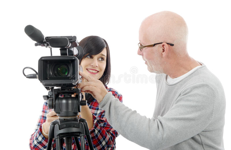 Young woman cameraman, and the mature man. Young brunette women cameraman, and the mature man royalty free stock photography
