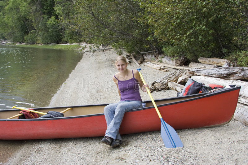 Young woman in a canoe holding the paddle. Clearwater Lake, Wells Gray Provincial Park, British Columbia, Canada stock image