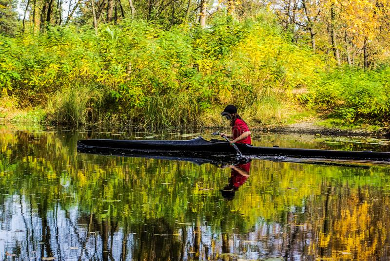 Young woman in canoe with oars swims on  river in jungle. Young woman in canoe with oars swims on  river in forest royalty free stock photo