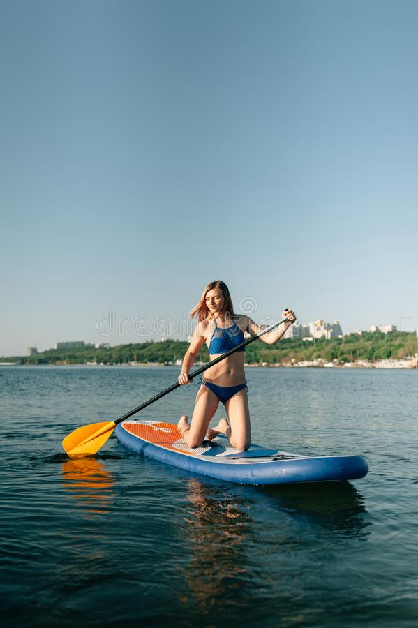Young woman canoeing in a lake. Woman paddling kayak on a summer day. royalty free stock photo