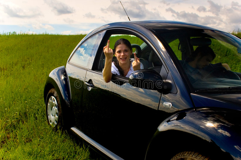 Young woman in car 1. A young woman makes a rude sign from her car seat stock photos
