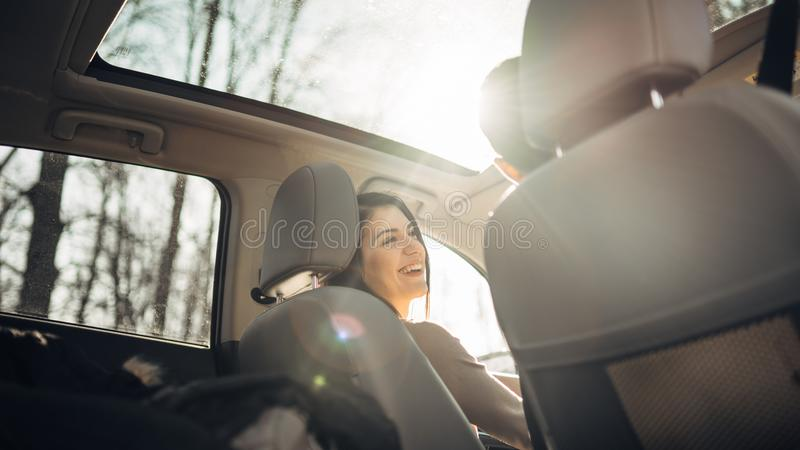 Young woman in a car,female driver looking at the passenger and smiling.Enjoying the ride,traveling,road trip concept.Driver royalty free stock photo