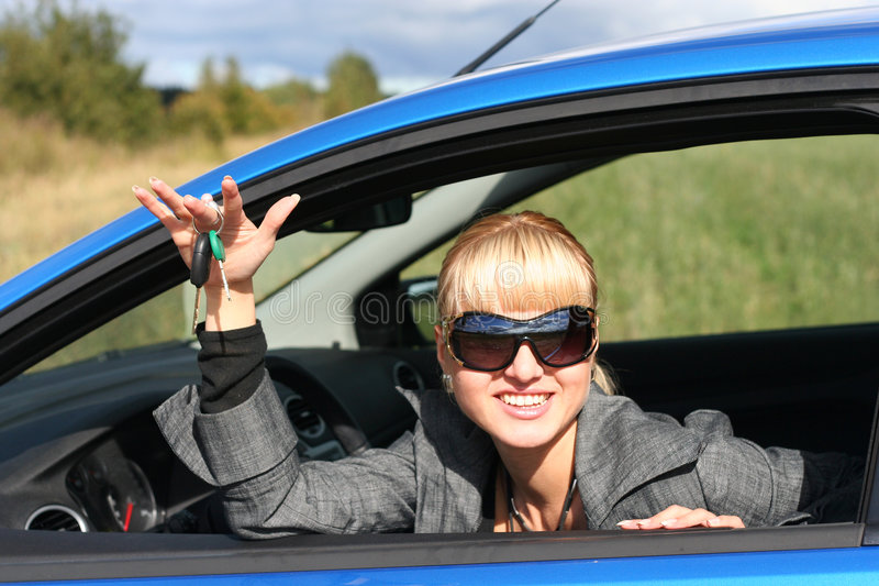 Young woman in car with key stock image