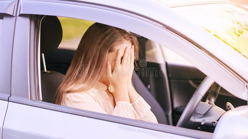Young woman in car. Ride instruction accident. Automobile loan.  stock photography