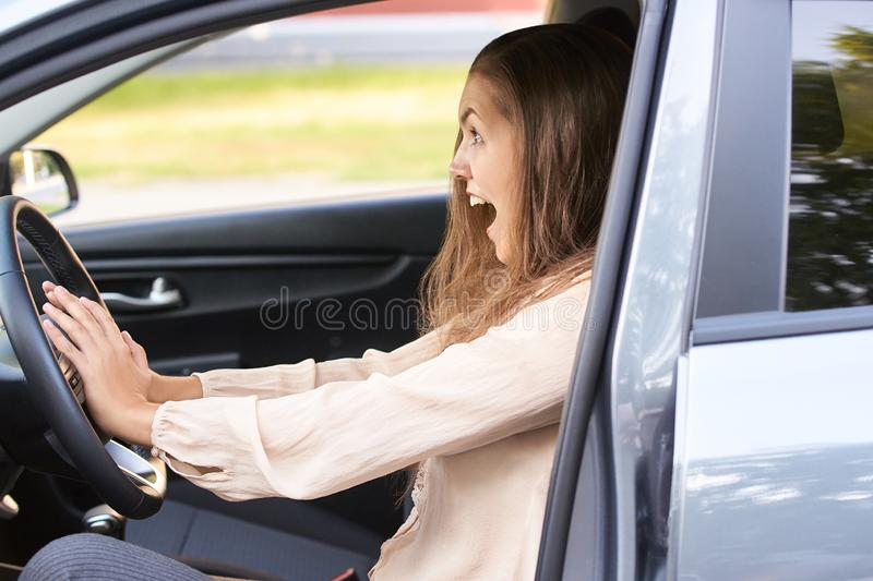 Young woman in car. Ride instruction accident. Automobile loan.  stock image