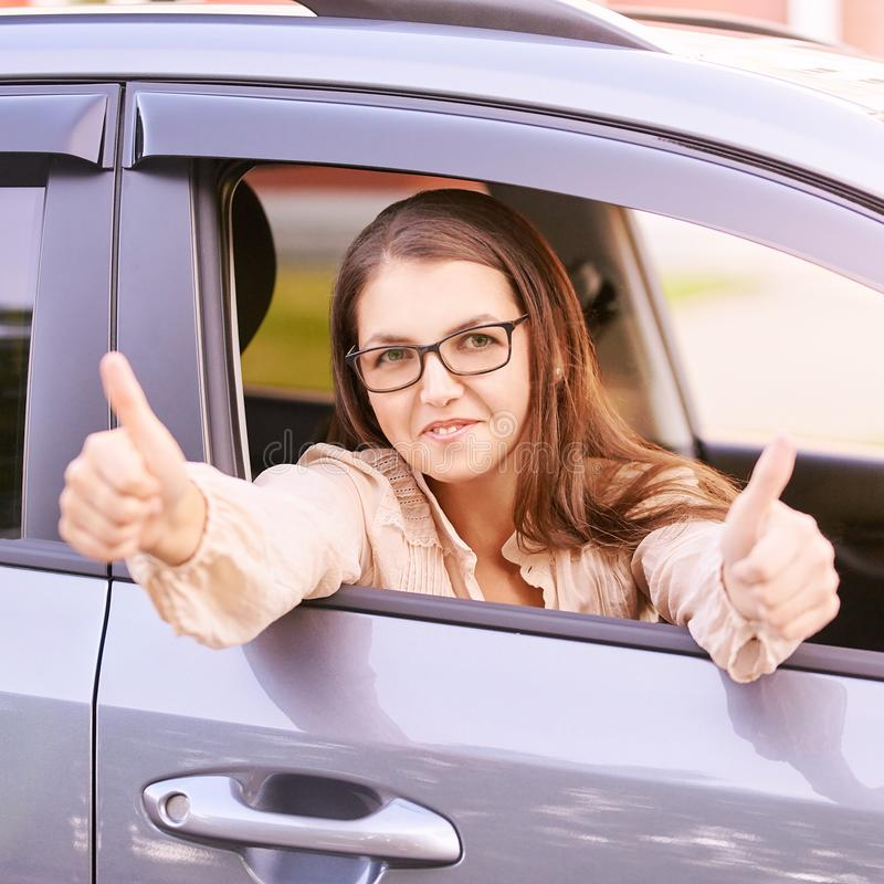 Young woman in car. Ride instruction. Automobile loan stock photography