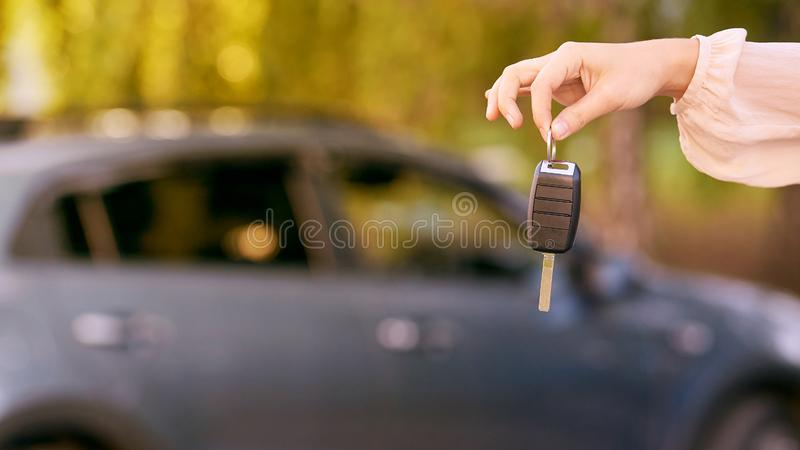 Young woman in car. Ride instruction. Automobile loan. Hand with key.  royalty free stock photography