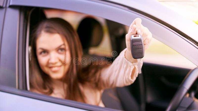 Young woman in car. Ride instruction. Automobile loan. Hand with key.  royalty free stock images