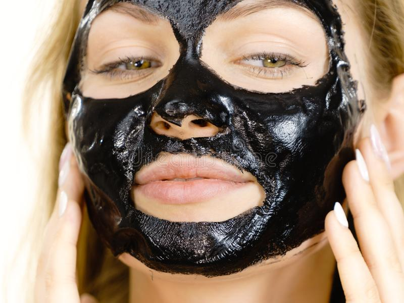 Girl with dried peel-off black mask on face. Young woman with carbo black peel-off mask on her face, cosmetic ready to remove, on white. Teen girl taking care of stock image