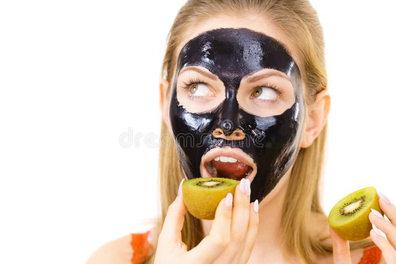 Girl black mask on face holds kiwi fruit. Young woman with carbo black peel-off mask on her face eating kiwi fruit halves, on white. Beauty treatment. Skincare stock photo