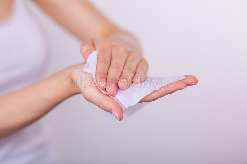 Woman carefuly cleaning hands with wet wipes. Young woman carefuly cleaning hands with wet wipes, white stock photo
