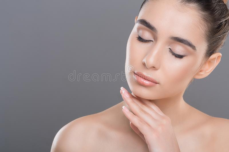 Young woman caressing her smooth soft skin. Natural skincare. Young woman caressing her smooth soft skin with closed eyes, copy space royalty free stock photography