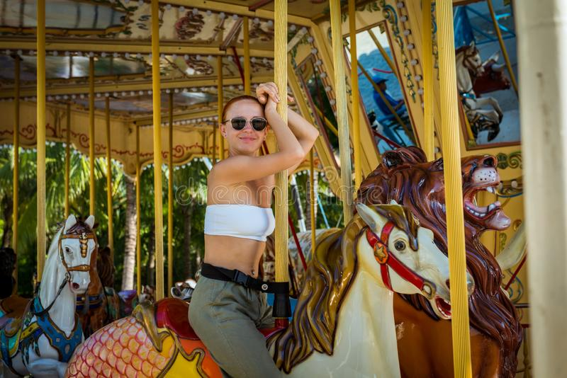 Young woman on carousel. Beautiful young woman wearing sunglasses playing on carousel merry-go-round stock image