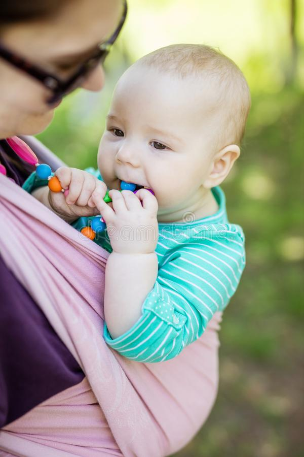 Young woman carrying her baby daughter in woven wrap outdoors in spring park. Baby girl chewing teething beads stock photo
