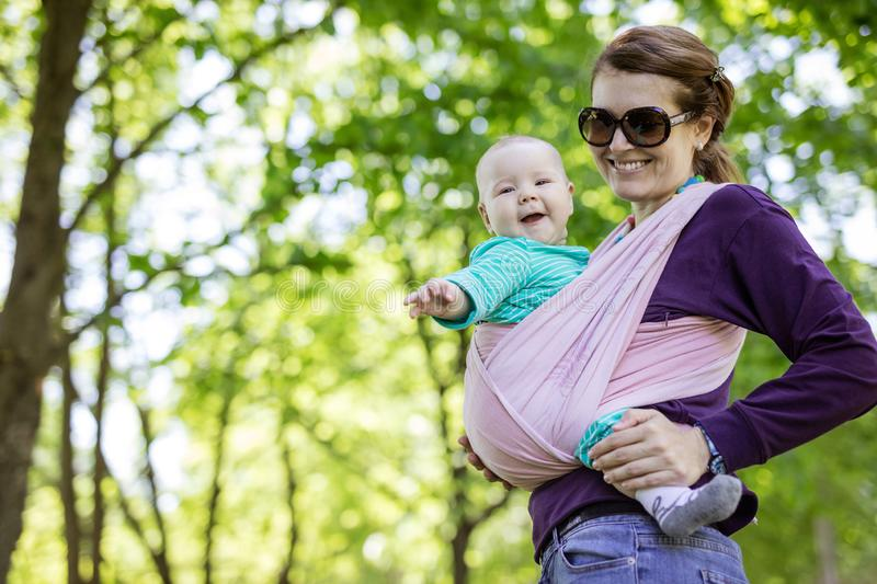 Young woman carrying her baby daughter in woven wrap outdoors in spring park stock images