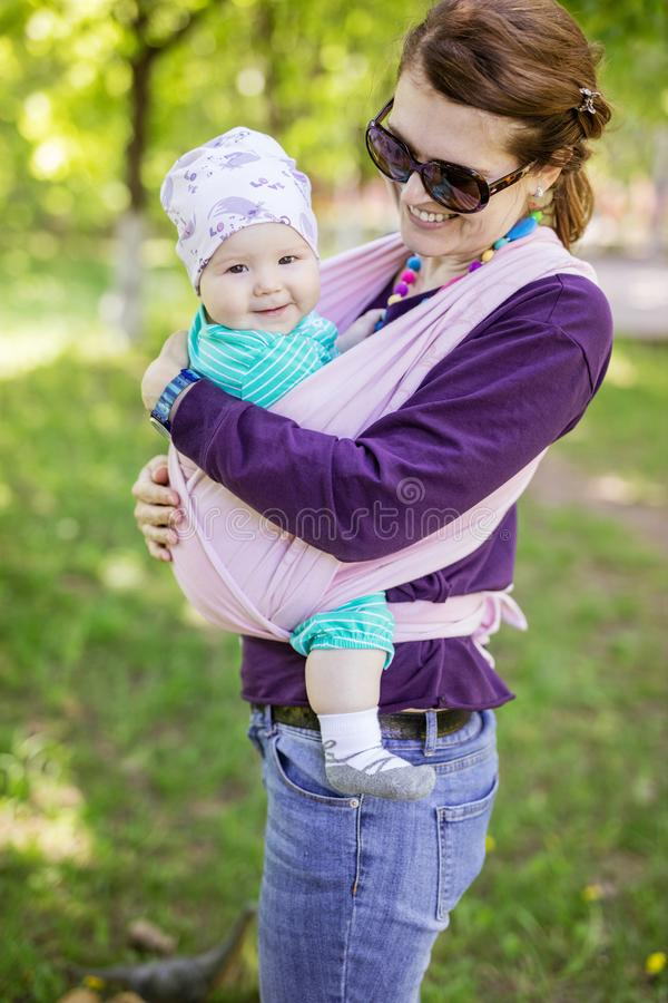 Young woman carrying her baby daughter in woven wrap outdoors in spring park royalty free stock image