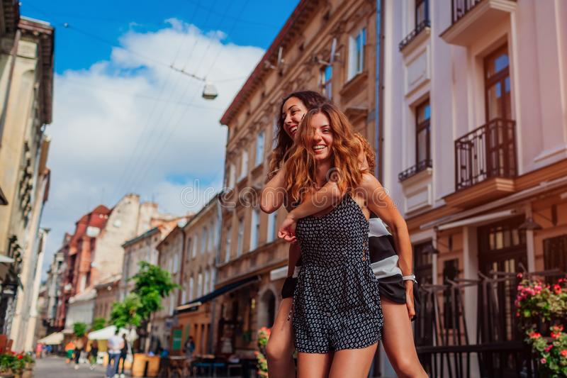 Young woman carrying her best friend on her back on city street. Happy girls laughing and having fun royalty free stock photography