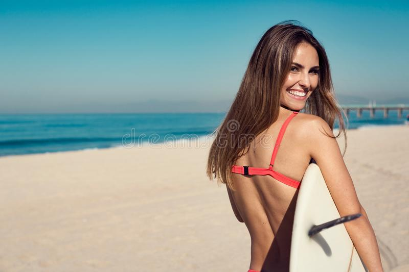 Young woman carrying a surfboard at the beach. Young woman carrying a surfboard at the beach in california royalty free stock photos