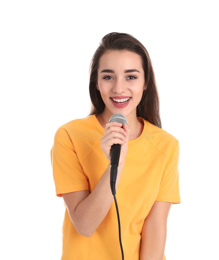 Young woman in casual clothes posing with microphone. On white background royalty free stock photography