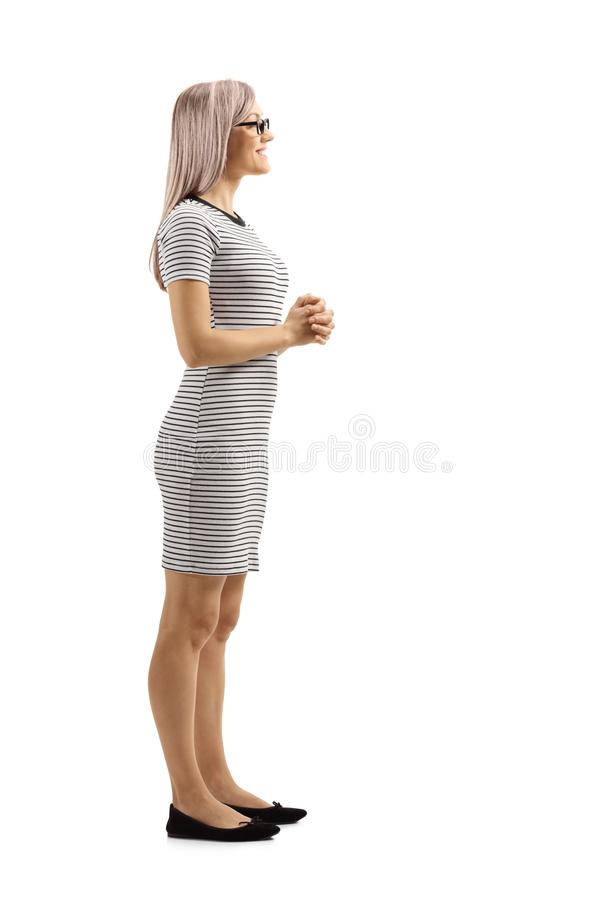 Young woman in a casual dress standing and listening. Full length profile shot of a young woman in a casual dress standing and listening isolated on white royalty free stock image