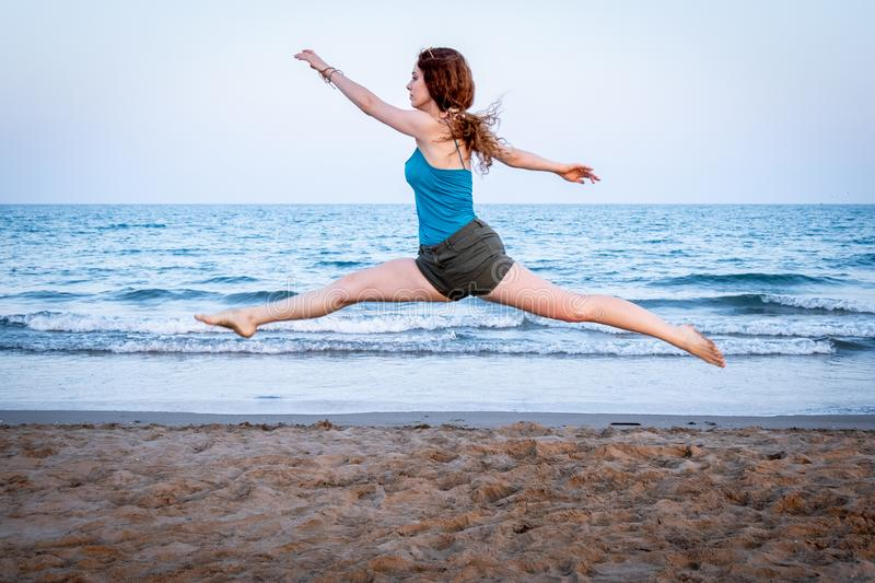 Young girl jumps on the sand of a Mediterranean beach at sunset royalty free stock images