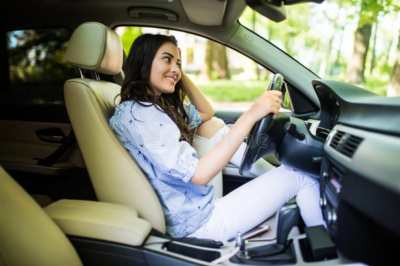 Young woman ooking over her shoulder while driving a car royalty free stock photo