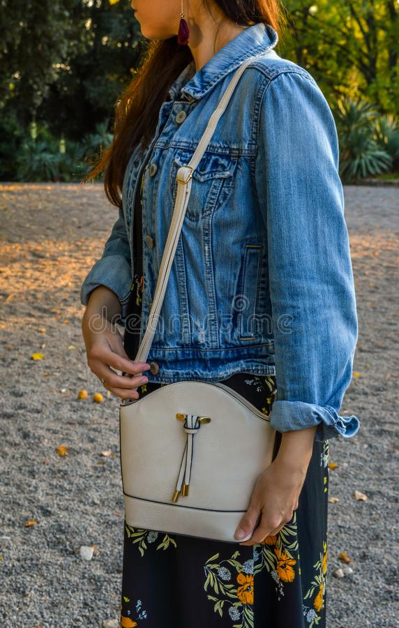 A young woman, casually dressed, with a mini bag over her shoulder stock photography