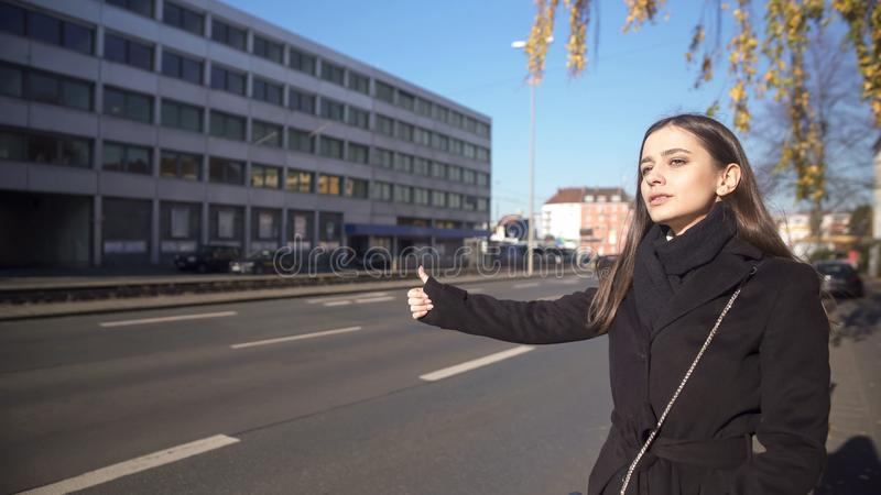 Young woman catching taxi on street in morning, late for work, hitchhiking stock photography