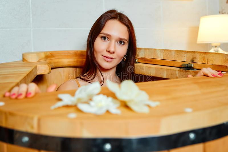 Young woman in cedar barrel. Spa ,medical procedures, skin care and treatment. Sauna and Hammam.  royalty free stock photos