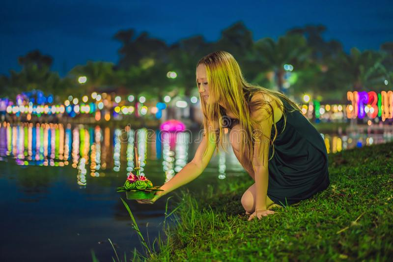 Young woman celebrates Loy Krathong, Runs on the water. Loy Krathong festival, People buy flowers and candle to light royalty free stock photo