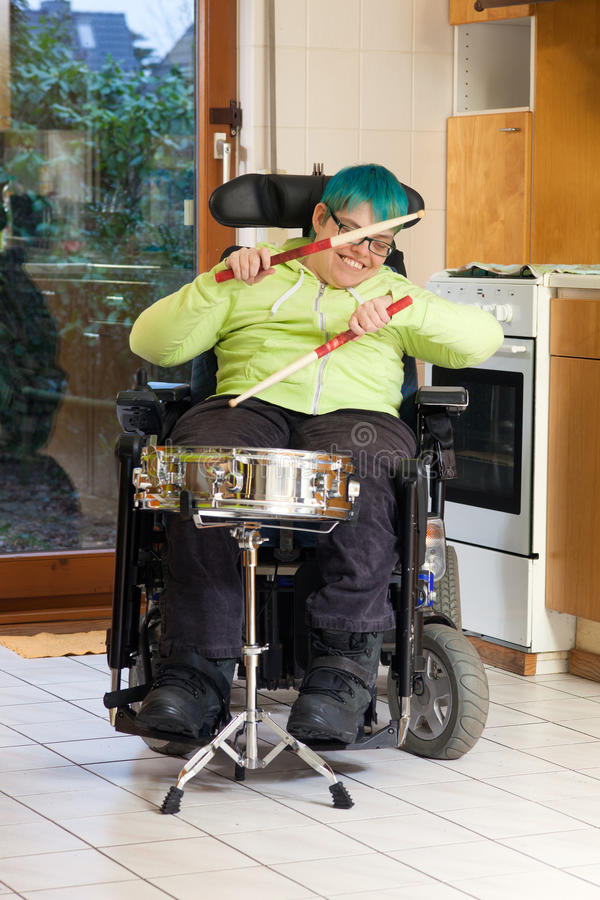 Young woman with cerebral palsy playing a drum. Young woman with infantile cerebral palsy caused by complications at birth sitting in a multifunctional royalty free stock photos
