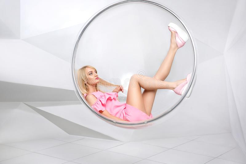 Young woman in a chair on a white background. Geometry. Blonde in a pink dress in a plastic round chair royalty free stock photography
